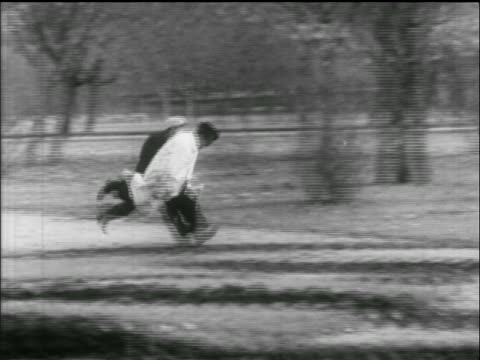 stockvideo's en b-roll-footage met pan 2 men run quickly through park / one trips / hungarian uprising - 1956