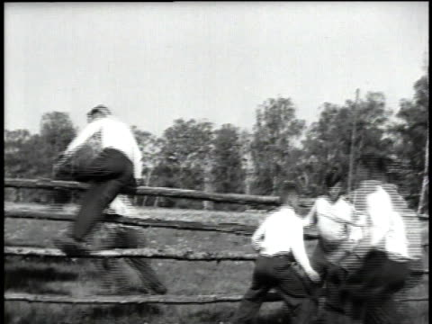men running across field jumping over a fence others helping / men scrambling over trees / men climbing a hill - ehemalige sowjetunion stock-videos und b-roll-filmmaterial
