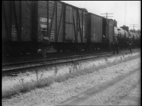 vídeos de stock, filmes e b-roll de b/w 1935 men running alongside jumping into slowly moving train - mendigo