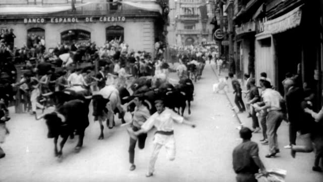 men running from charging cow bulls down the streets of pamplona / spectators watching from balcony / bulls charging around corner narrowly missing... - charging sports stock videos & royalty-free footage