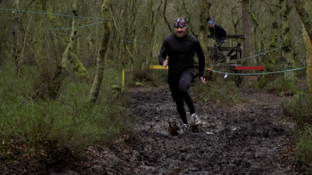 men running in mud run through woodland - slow motion - survival stock videos and b-roll footage