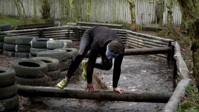Men running through bog water in Mud run obstacle course / assault course - Slow motion