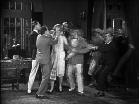 b/w 1926 men (charley chase) rushing to rescue of woman being choked by man + punches him / feature - 1926 stock-videos und b-roll-filmmaterial