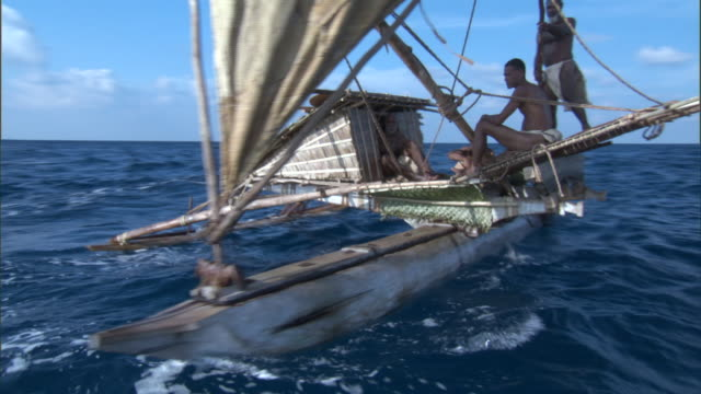 Men sail on outrigger canoe, Duff Islands, Solomon Islands