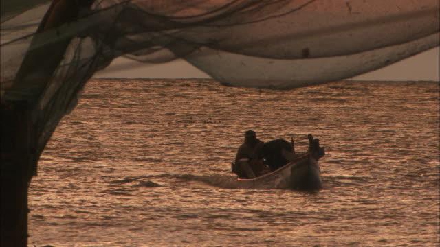 vídeos de stock e filmes b-roll de men sail small fishing boat towards shore available in hd. - rede de pesca comercial