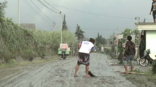 men scrape volcanic ash mud off road after eruption of merapi volcano; indonesia. 7 november 2010 / audio - indonesia volcano stock videos & royalty-free footage