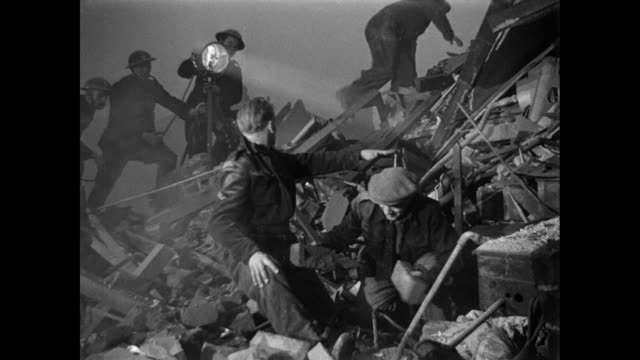 stockvideo's en b-roll-footage met renactment men searching through bomb rubble looking for survivors and asking others to be quiet / united kingdom - 1946