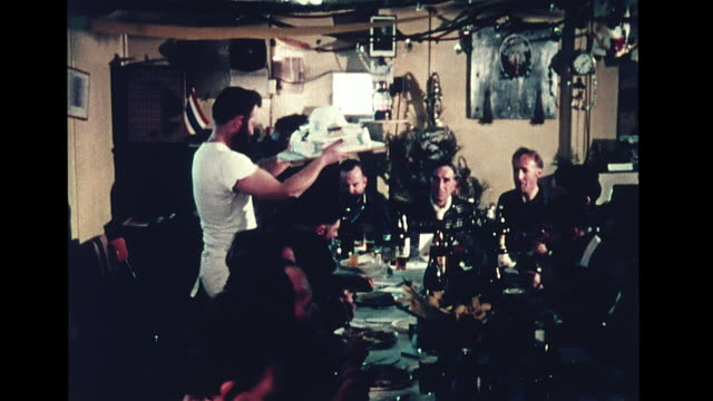 stockvideo's en b-roll-footage met vs men seated at long table in station dining room main course being served to table vs men eating la ms penguin chick eating something out of bowl... - dining room