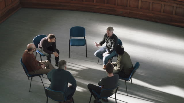Men seated in a circle at therapy session