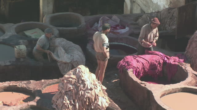 ms men selecting skins in leather / fez, fã¨s-boulemane, morocco - 染料点の映像素材/bロール