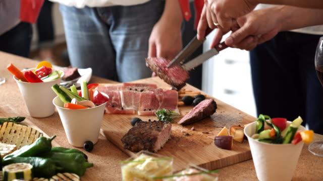 男性は各皿に肉を提供します。 - パーティー点の映像素材/bロール