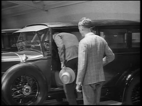 b/w 1928 2 men shaking hands + couple gets in new lincoln car in lot / newsreel - 1928 stock-videos und b-roll-filmmaterial