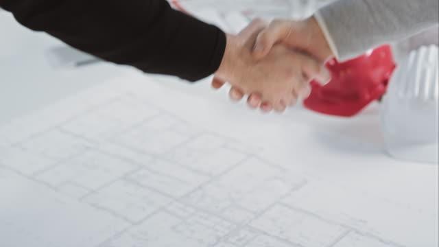 SLO MO Men shaking hands over the floor plan