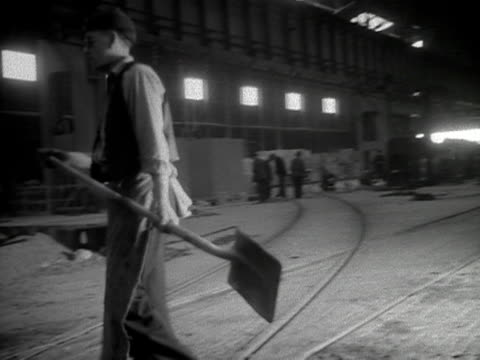 men shovel pig iron into the blazing furnaces at the shotton steelworks in north wales 1953 - skibrille stock-videos und b-roll-filmmaterial