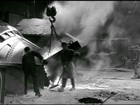 Men shoveling ash from floor into furnace Steel mill or factory workers pouring molten metal into furrow shapped mold
