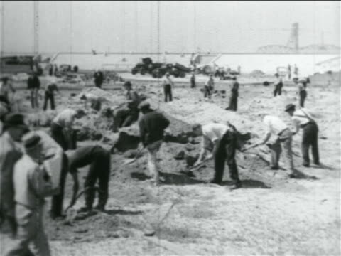 b/w 1934 men shoveling dirt in wpa stadium construction project / documentary - 1934 stock videos & royalty-free footage