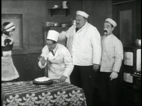 b/w 1920 2 men (1 is snub pollard) shoving chef's face into pie on table + exit quickly / short - domestic staff stock videos & royalty-free footage