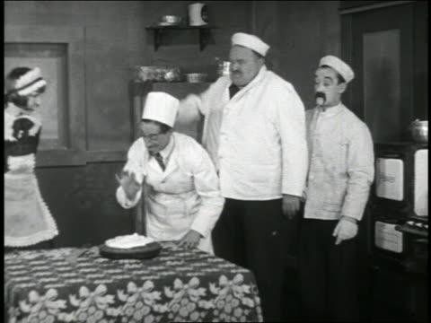 b/w 1920 2 men (1 is snub pollard) shoving chef's face into pie on table + exit quickly / short - collaboratore domestico video stock e b–roll