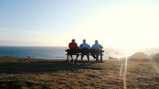 men sit on bench at sunset