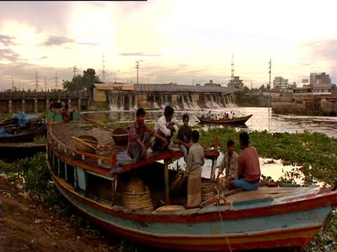 vídeos y material grabado en eventos de stock de men sit on boats in front of a pumping station used for flood waters - estación de bombeo