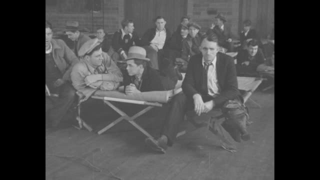 Men sitting and lying on cots in shelter after fire destroyed their bunkhouse / Note exact month/day not known