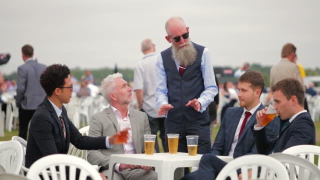männer sitzen um einen tisch, ein paar bier zu genießen - 30 34 jahre stock-videos und b-roll-filmmaterial