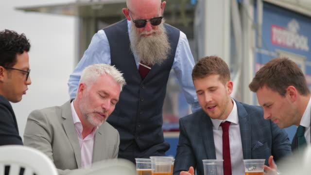 vídeos de stock e filmes b-roll de men sitting around a table enjoying a few beers - newcastle upon tyne
