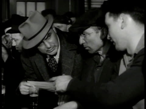 men sitting at bar w/ drinks talking over paperwork man handing paper to worker to sign dramatization int man standing speaking to workers 'each... - labor union stock videos and b-roll footage