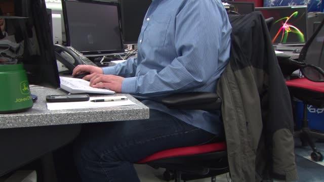 Men Sitting At Computer Desks From The Waist Down