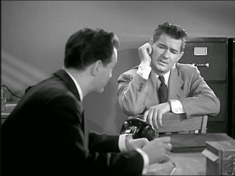 b/w 1949/50 2 men sitting at desk having casual discussion / one sitting in chair backwards - kompletter anzug stock-videos und b-roll-filmmaterial