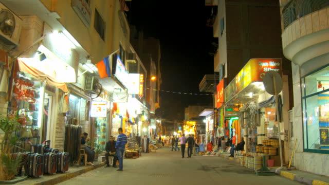 ws men sitting at illuminated night market / hurghada, red sea coast, egypt - hurghada stock-videos und b-roll-filmmaterial