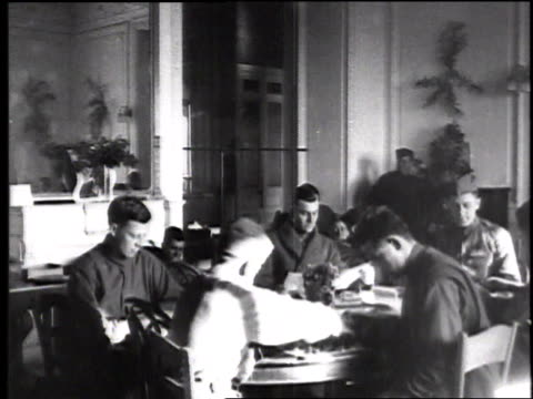 men sitting at tables in large room reading, relaxing and playing games / france - draughts stock videos & royalty-free footage