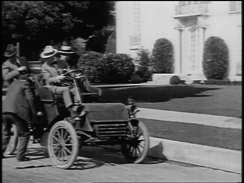 b/w 1904 men sitting in model a car as man cranks it / they drive away from curb / newsreel - 1904 stock videos & royalty-free footage