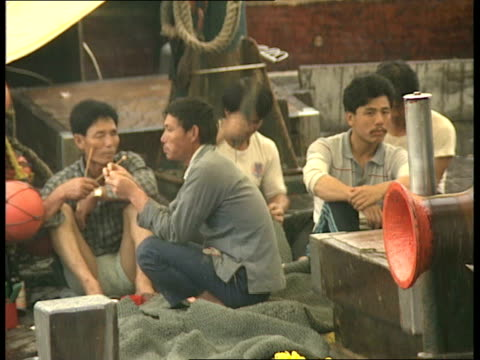 vidéos et rushes de men sitting on boat fixing nets / men standing on junks int men playing board game mah jong ext man cleaning fish / cat on lead / men repairing nets - jonque