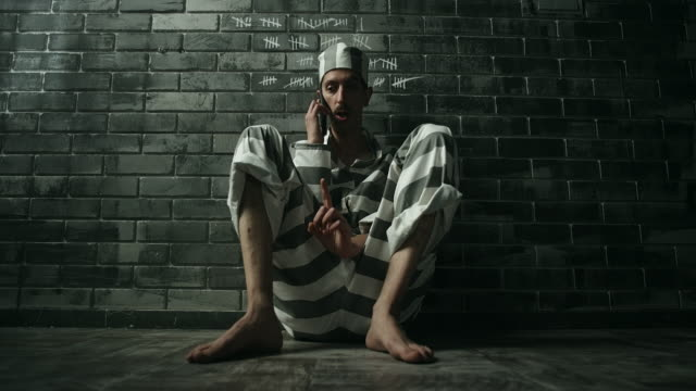 men sitting on floor and talking on phone in prison cell - whispering stock videos & royalty-free footage