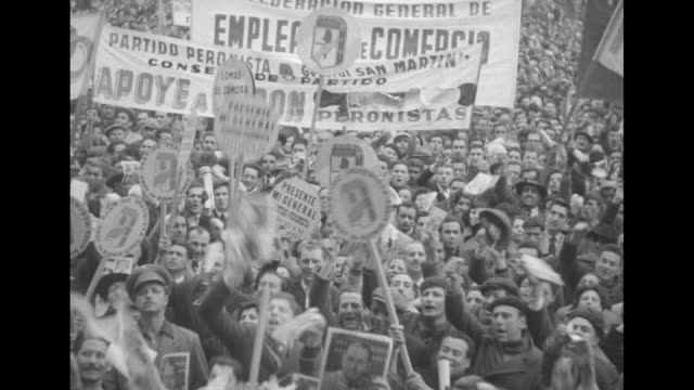 vídeos de stock e filmes b-roll de men sitting on lampposts in plaza de mayo / vs large crowds jumping shouting some people have banners declaring presence of various labor groups... - 1955