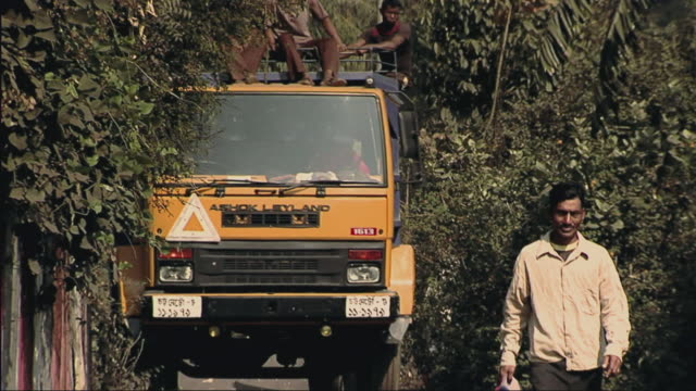 ws zi men sitting on truck roof rack, man walking in foreground / chittagong, bangladesh - legs crossed at ankle stock videos and b-roll footage