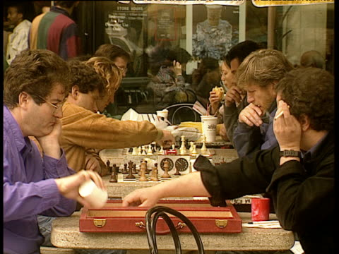 men sitting opposite each other outside cafe playing chess and backgammon - harvard university stock videos and b-roll footage