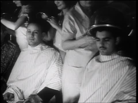 b/w 1931 pan 2 men sitting under hair dryers in beauty shop / toledo, ohio / newsreel - 衣類乾燥機点の映像素材/bロール