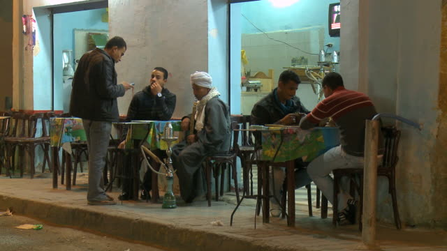 ms men sitting with hukka outside cafã© at night / hurghada, red sea coast, egypt - hurghada stock-videos und b-roll-filmmaterial