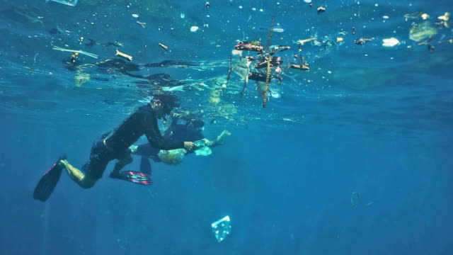 men snorkeling in ocean surrounded by plastic pollution and garbage environmental emergency - responsibility stock videos & royalty-free footage