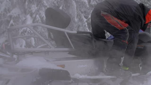 stockvideo's en b-roll-footage met men snowmobiling in the mountains. - slow motion - men