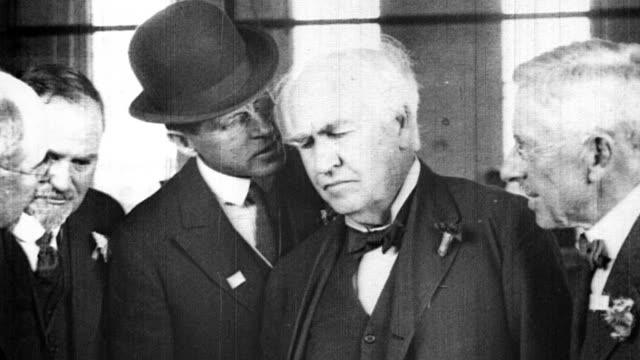 vídeos de stock e filmes b-roll de men speaking closely into thomas edison's ear as he tours the general electric plant and reviews machinery. thomas edison visiting general electric... - general electric