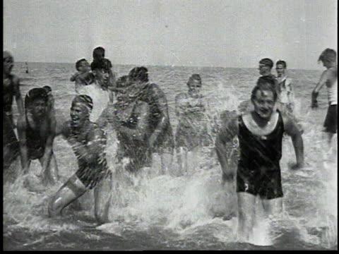 vídeos de stock e filmes b-roll de men splashing in surf / man diving off of a board on shore - 1934