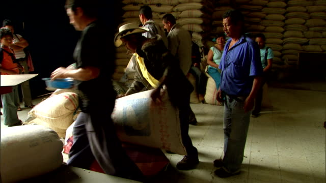 men stack bags of coffee bean in a warehouse. - 麻袋点の映像素材/bロール