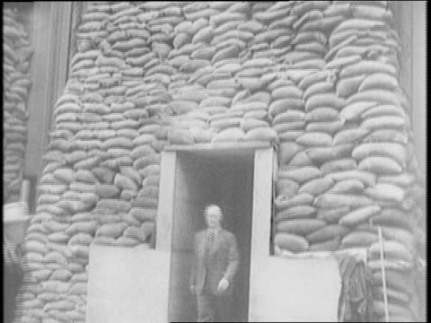 men stack sandbags in front of pacific telephone and telegraph company building / facade of building / men in coveralls paint the wing of a martin... - telegraph machine stock videos & royalty-free footage