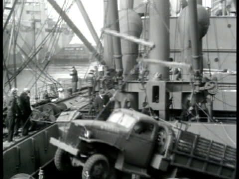 vídeos de stock e filmes b-roll de men stacking boxes truck lowered into cargo hold by crane docks w/ many jeeps parked fg covered supplies bg parked artillery antiaircraft gun truck... - baixar