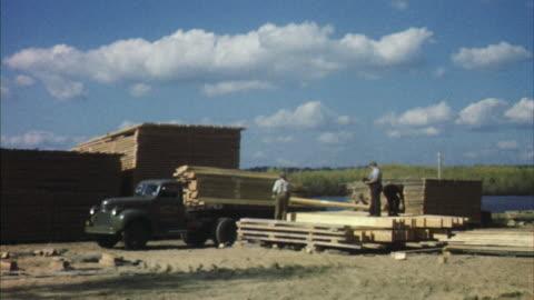 ms men stacking lumber next to truck - timber yard stock videos & royalty-free footage