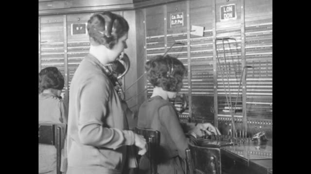 Men stand and sit at telephone switchboard / engineer stands at racks of telephone machinery / female operators sit at switchboards Operator Eileen...