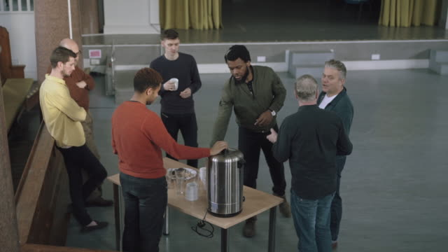 Men stand around a table and chat during coffee break